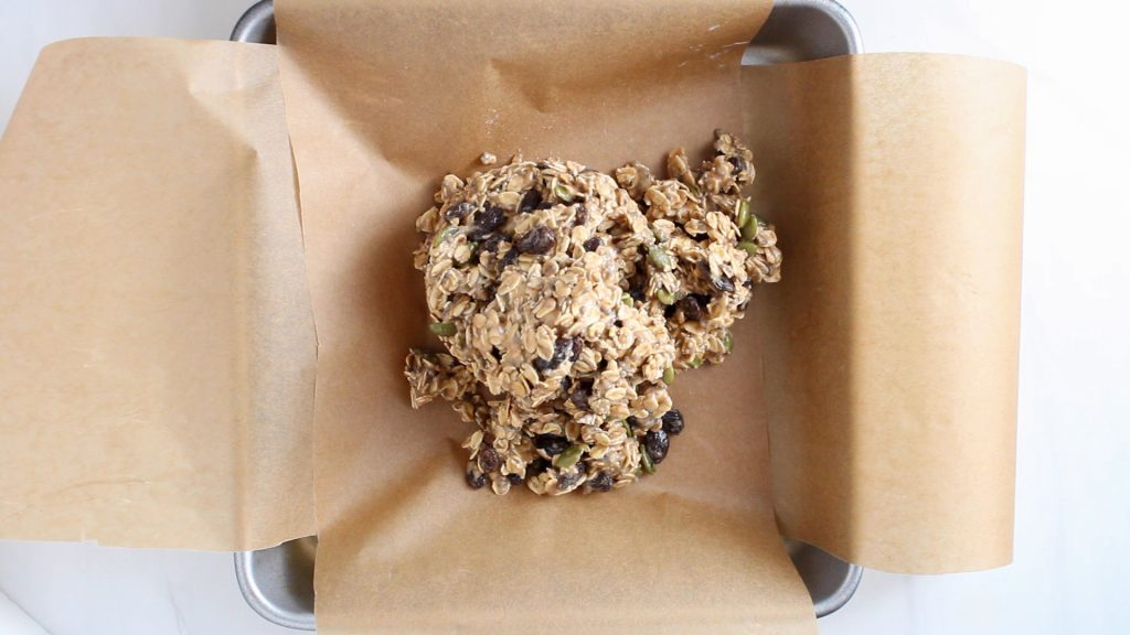 There is square cake pan that's covered in parchment paper with a oatmeal and raisin mixture on it.