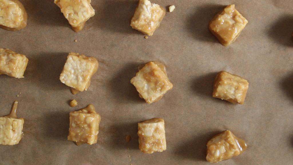 There are a few cubes of marinated soy bean products spread on a baking sheet and just about to be cooked in the oven