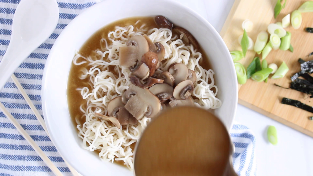 There is a large ladder pouring some brothy soup on top of Asian style noodles.