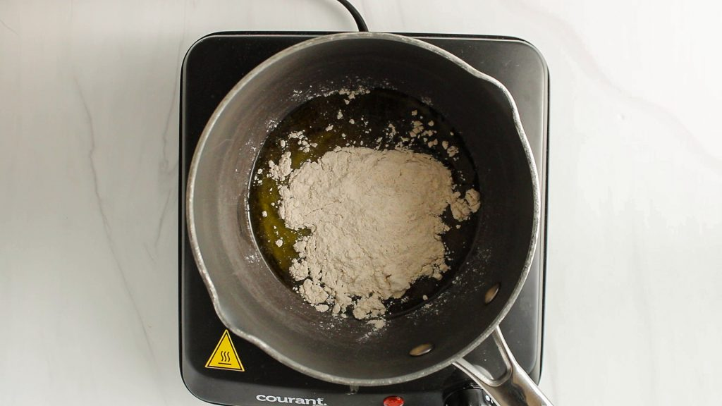 There is olive oil and flour in a sauce pan.