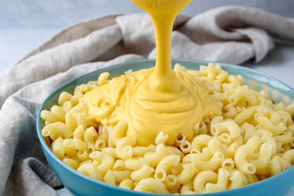 There is a cheesy pasta sauce being poured over a blue bowl containing cooked noodles. There is a beige hand towel in the background.