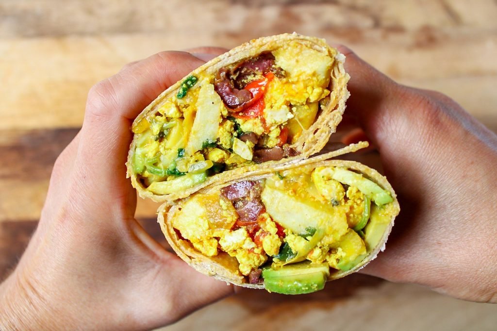 There are 2 hands holding 2 halves of tofu scramble breakfast burrito showing the inside.