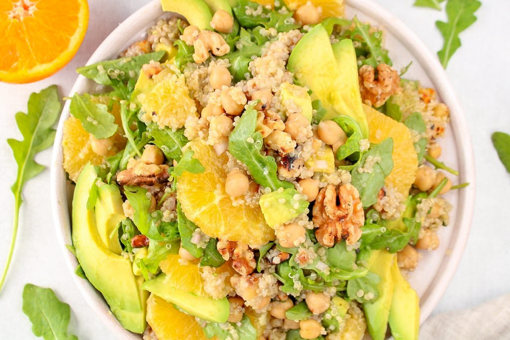 In a large shallow bowl, there is a quinoa avocado salad including oranges and arugula. On the side, there are half oranges, arugula leaves and a avocado cut in half.