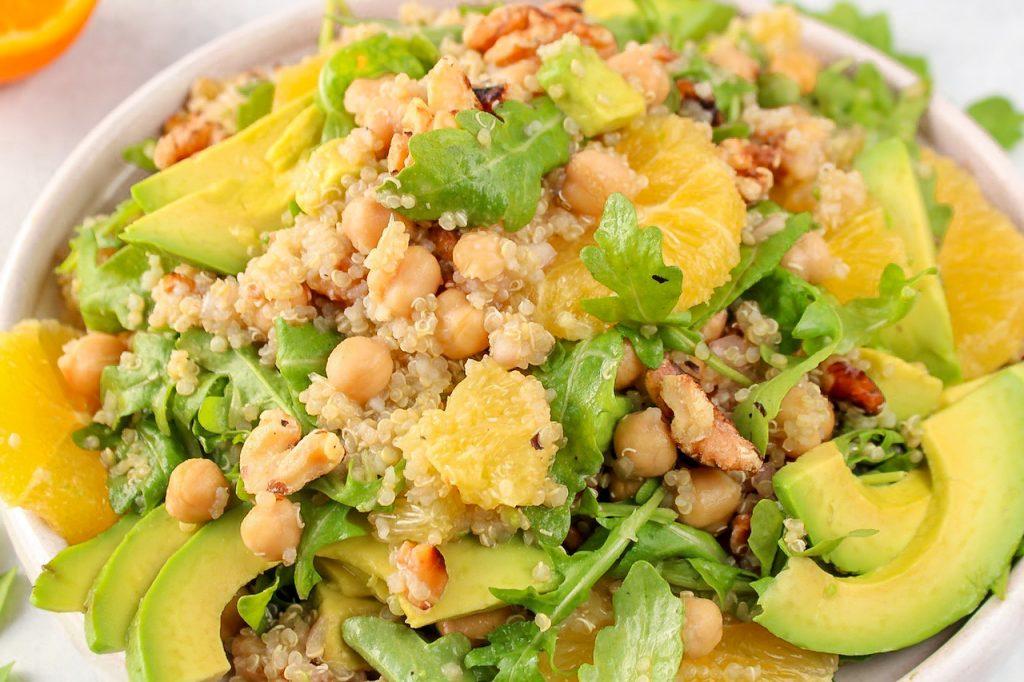 Close-up on a quinoa avocado salad with oranges and arugula.