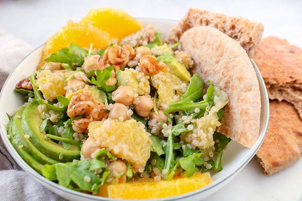 Close up on a quinoa salad containing oranges, arugula, avocado, walnuts and chickpeas. There are pieces of pita bread on the side.
