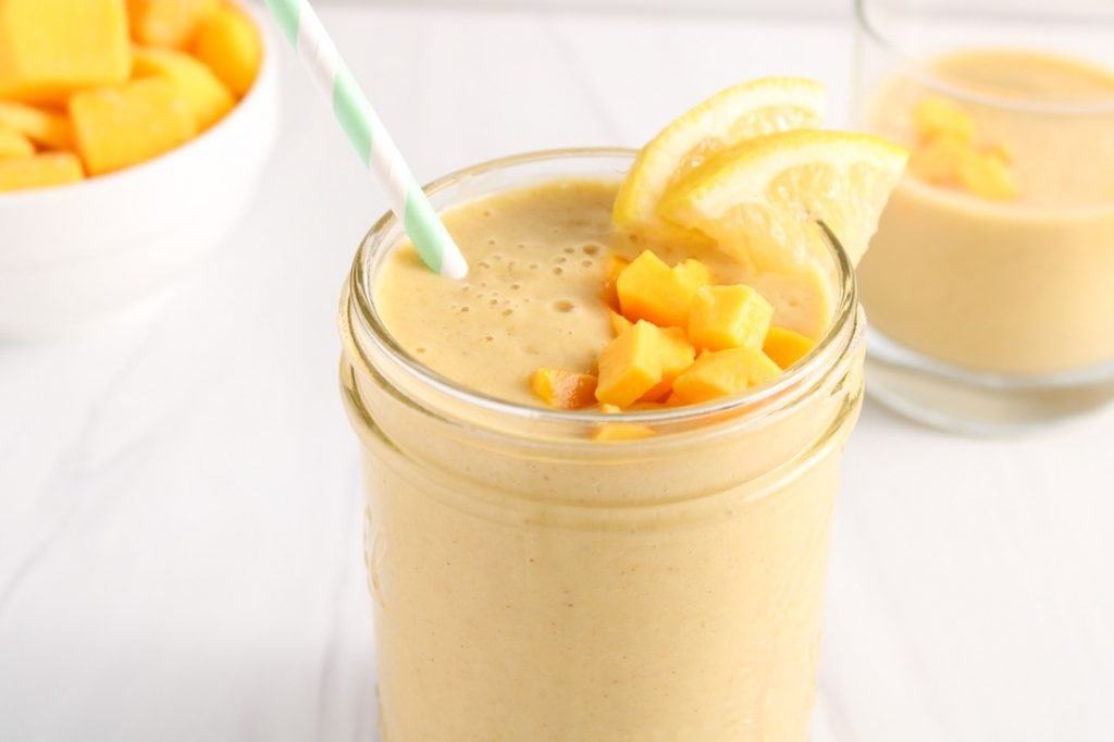 There is a oat milk mango smoothie in a see through glass jar topped with chopped mango and lemon slices. There are mango chunks in a white bowl in the background and a small glass of smoothie.