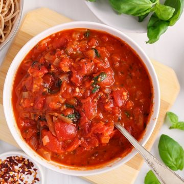 There is a hearty marinara sauce in a white bowl surrounded by a few bowls containing cooked noodles, fresh basil, dried herbs, garlic and red pepper flakes.
