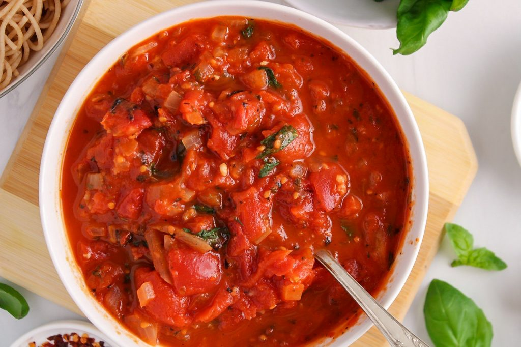 There is a hearty marinara sauce in a white bowl surrounded by a few bowls containing cooked noodles, fresh basil and red pepper flakes.