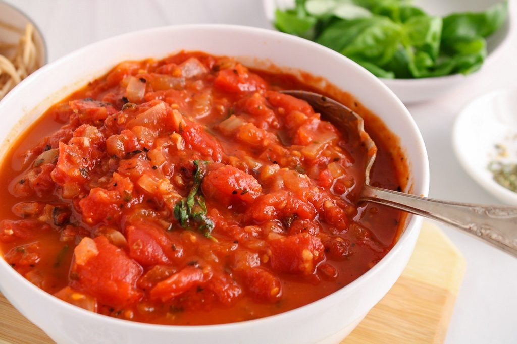 There is a hearty marinara sauce in a white bowl with a large spoon inside. There is fresh basil in the background and cooked noodles.