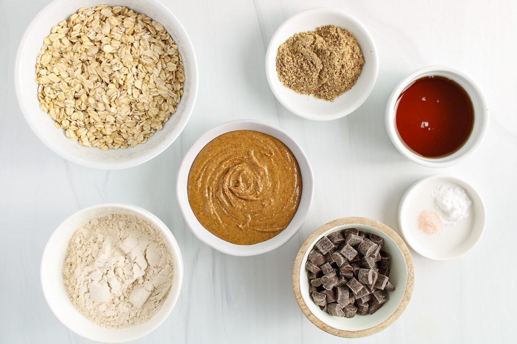 Ingredients needed to make this recipe: raw oats, whole wheat flour, almond butter, ground flax seeds, maple syrup, baking powder, salt and chocolate chips.