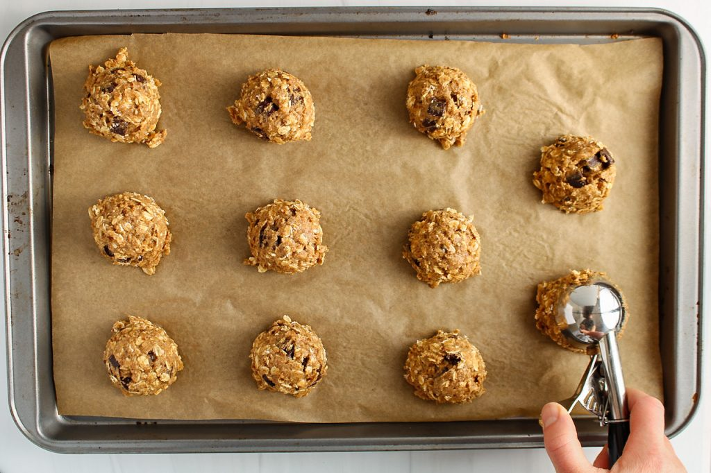 There is a baking sheet with balls of raw cookie dough being distributed. You can see a hand spreading the balls using an ice cream scoop. (In process picture)