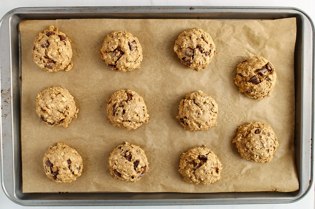 There are some vegan oatmeal chocolate chip cookies on a baking sheet.