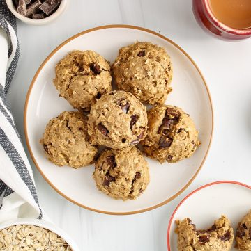 There are 6 vegan oatmeal chocolate chip cookies on a white plate and surrounded by a grey and white hand towel, a cup of tea, dark chocolate chip in a small bowl and a large white bowl containing raw oats.