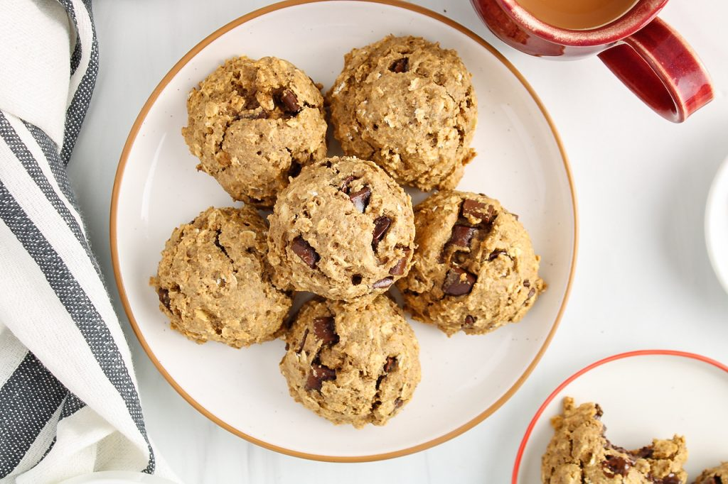 There are 6 vegan oatmeal chocolate chip cookies on a white plate and surrounded by a grey and white hand towel and a cup of tea.