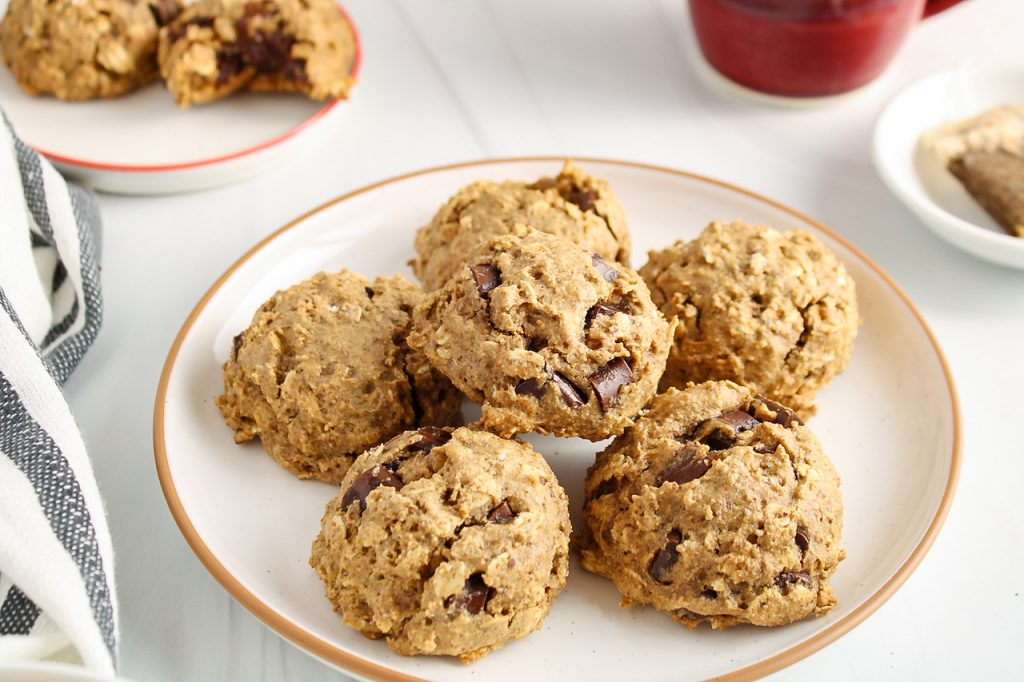 There are 6 vegan oatmeal chocolate chip cookies on a white plate surrounded by a grey and white hand towel, a cup of tea and a cookie with a bite off in the background on a different plate.