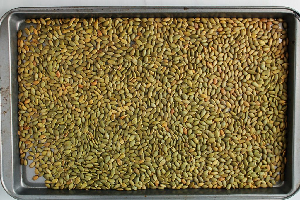 There are roasted pumpkin seeds filling a baking sheet