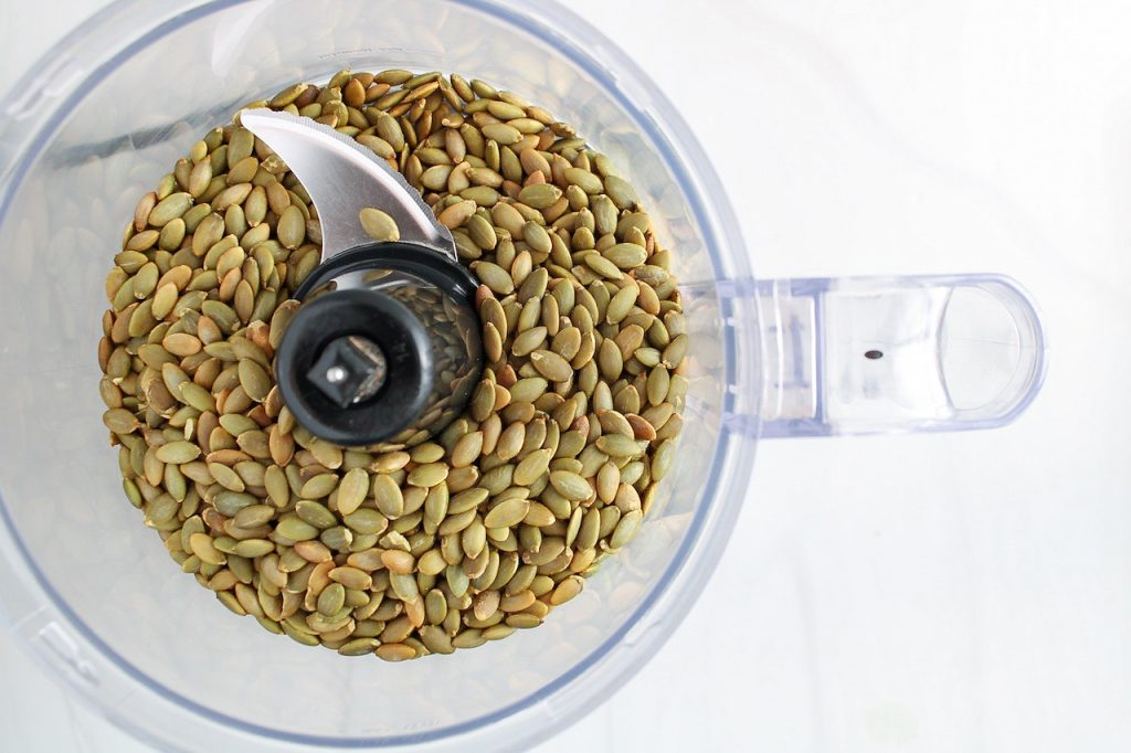 There are roasted pumpkin seeds in a food processor