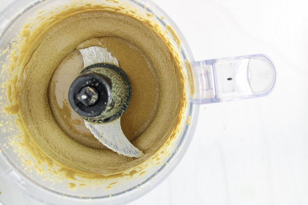 There is a creamy green mixture in a food processor