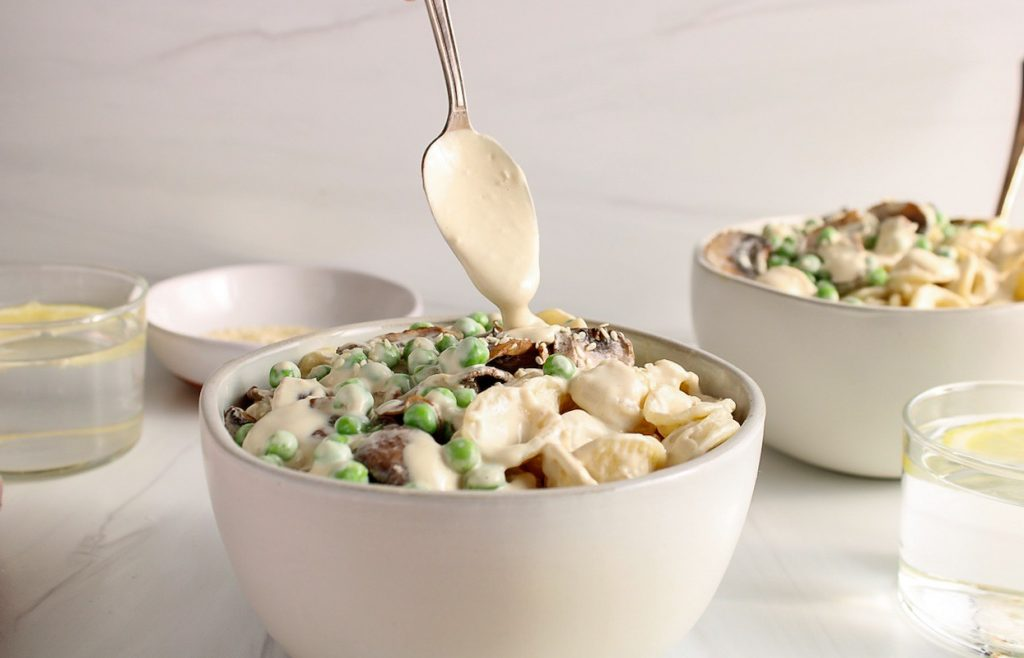 There is a spoon drizzling a tahini sauce over a bowl with tahini pasta that's topped with green peas and mushroom. There is another bowl with pasta in the background as well as 2 glasses of water and a small bowl with some sesame seeds.