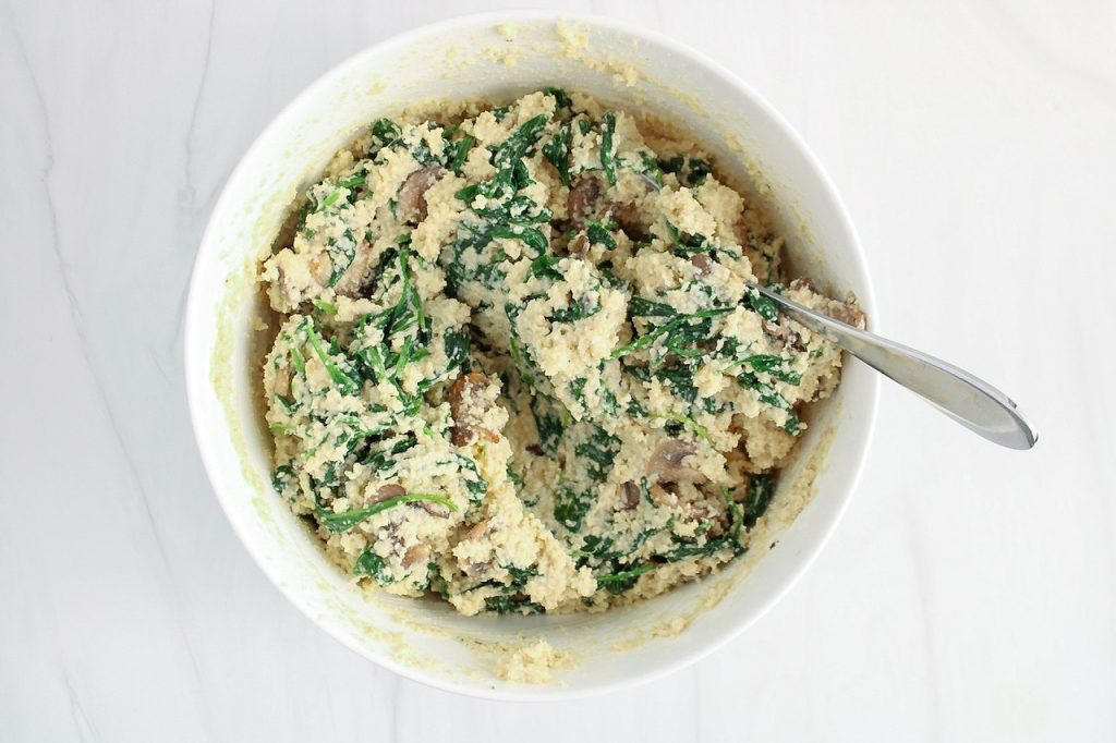 There is a white bowl with a creamy mixture containing spinach and mushroom with a spoon on the side used to stir.