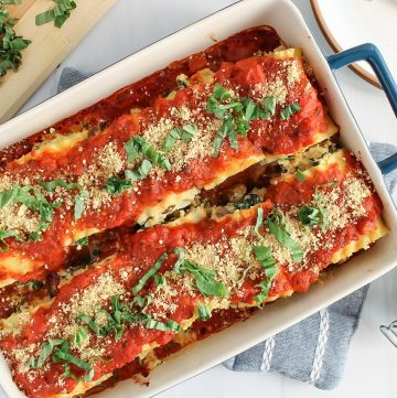 There are vegan lasagna roll-ups in a blue baking dish with plate and forks on the side as well as vegan parmesan cheese and chopped fresh basil.