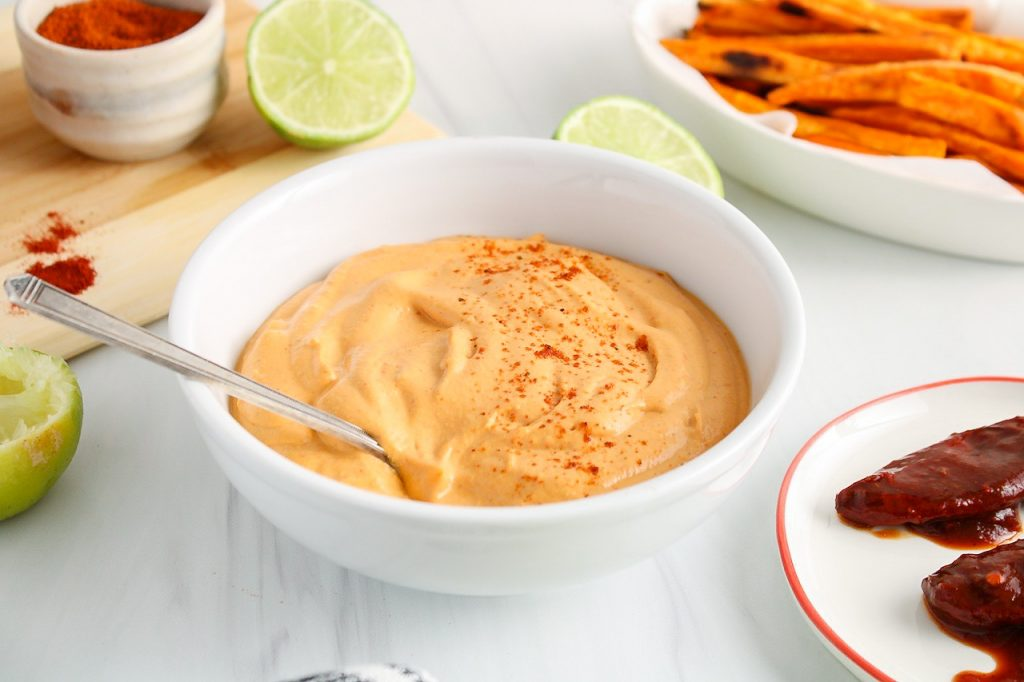 There is a vegan chipotle mayo in a white bowl with a spoon inside, surrounded by fresh limes, sweet potato fries, chipotle peppers and different spices.