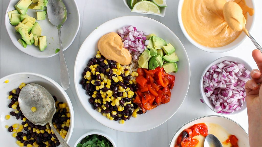You can see a hand layering a few ingredients in a bowl (brown rice, avocado, bean and corn, cilantro, a chipotle sauce and roasted red pepper)