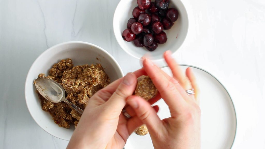 There are 2 hands pressing on a sticky brown mixture made out of dates. There are more of the mixture in the background as well as a white bowl with frozen cherries.