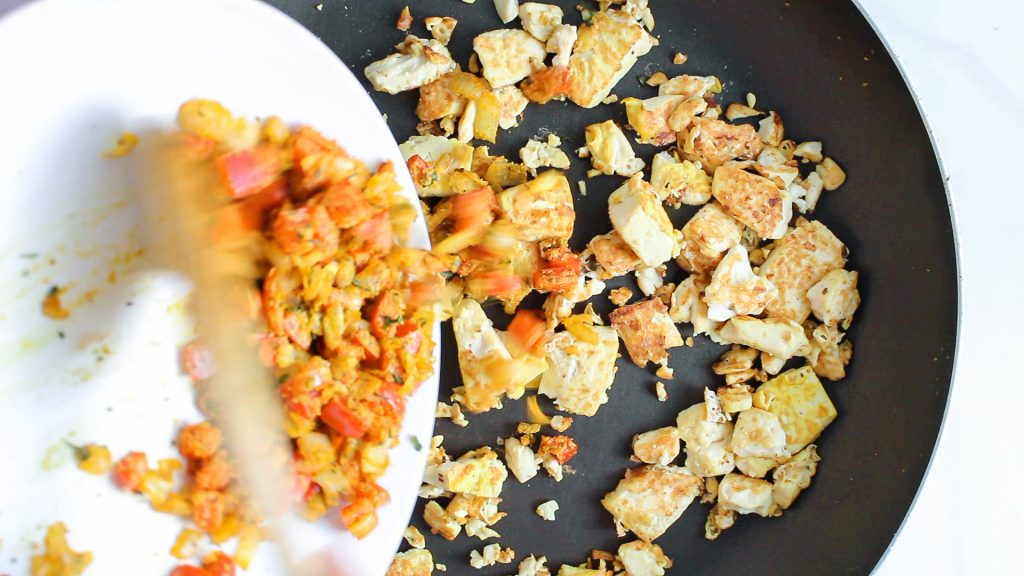 There are chunks of tofu cooking in a pan while some diced vegetable are added to the pan.