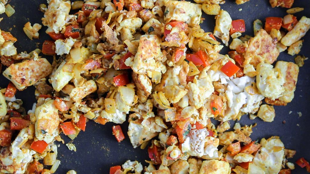 There are some diced onion, red pepper, tofu and garlic cooking in a pan with spices.