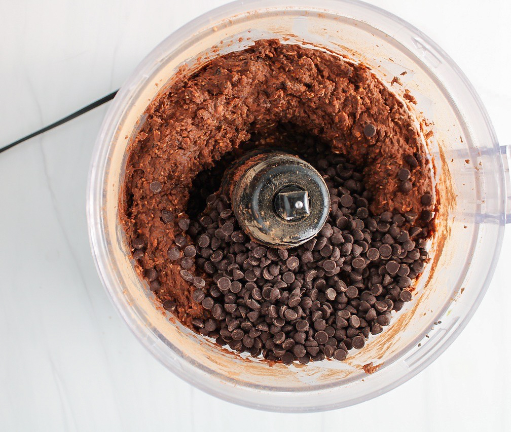 Showing inside a food processor containing a creamy chocolate mixture and topped with chocolate chips.