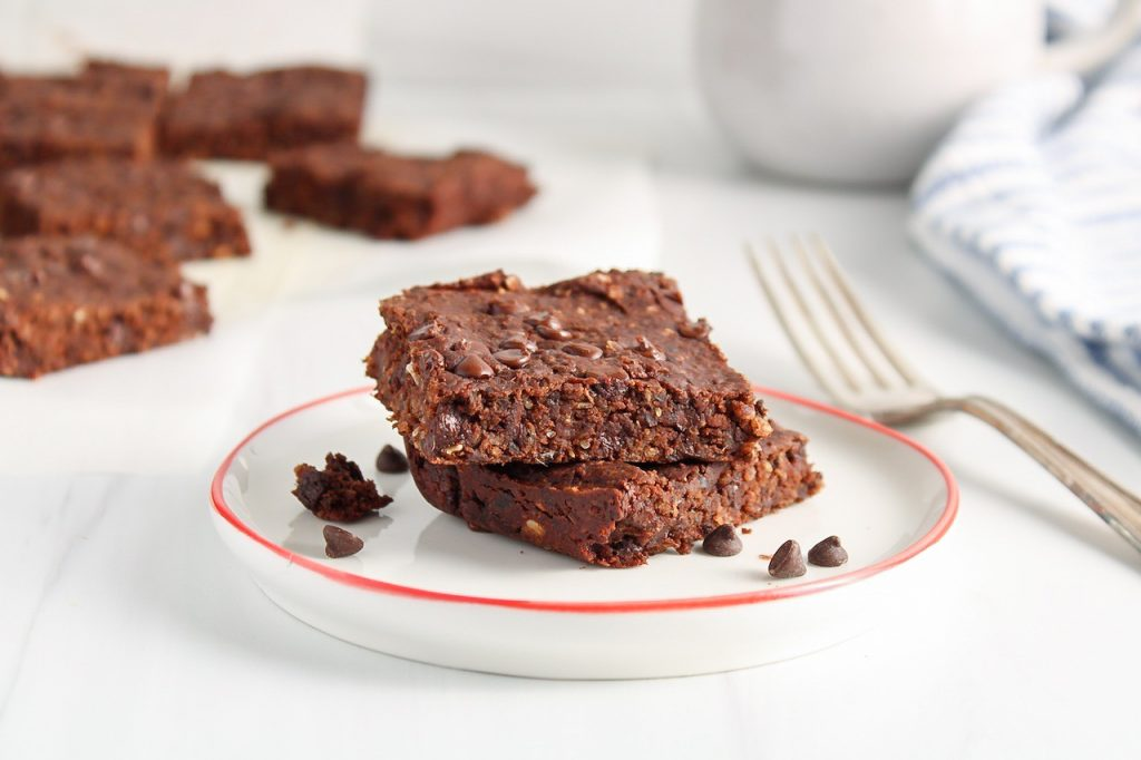 There are 2 squares of vegan black bean brownies on a small white plate with more brownies in the back, a coffee mug, a fork and a white and blue hand towel.