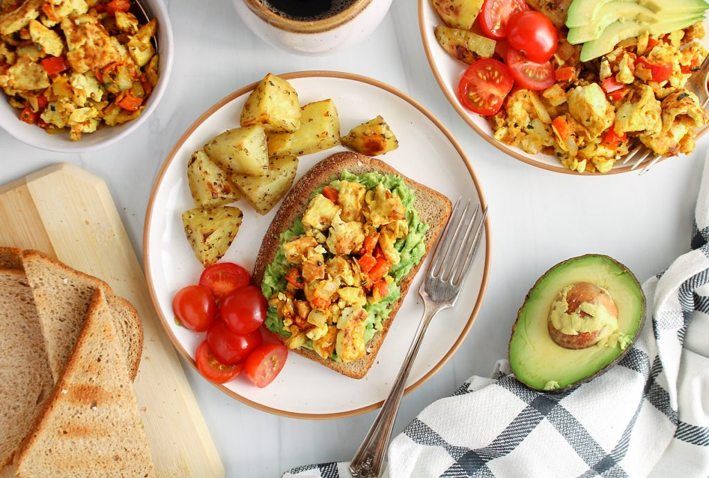 There are roasted potatoes, sliced cherry tomatoes as well as a slice of bread topped with mashed avocado and a silken tofu scramble. There is half of an avocado on the side of the plate, another plate with some of the scramble, more toasts and a white and black hand towel.