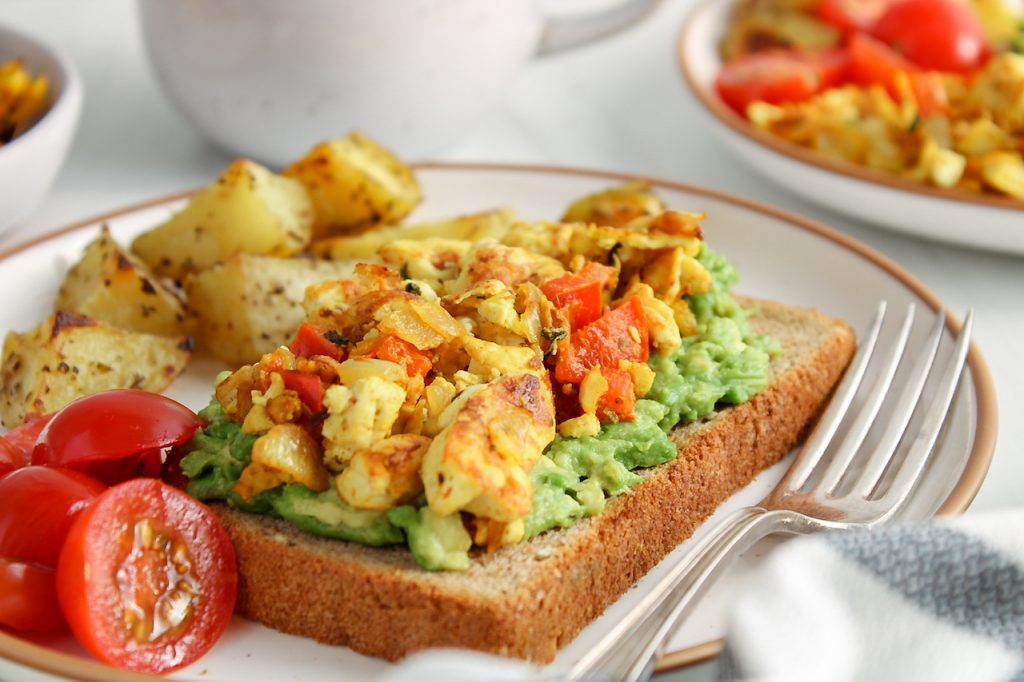 There are roasted potatoes, sliced cherry tomatoes as well as a slice of bread topped with mashed avocado and a silken tofu scramble.