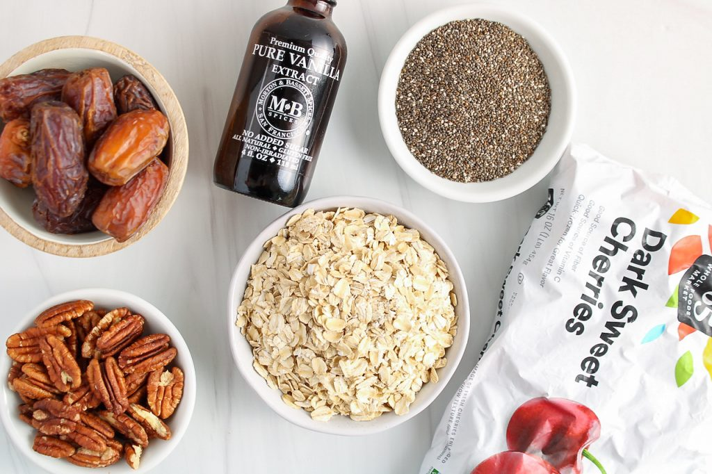 There are a few small white bowls containing dates, pecans, raw oats, chia seeds as well as a bottle of vanilla extract and a bag of frozen cherries.