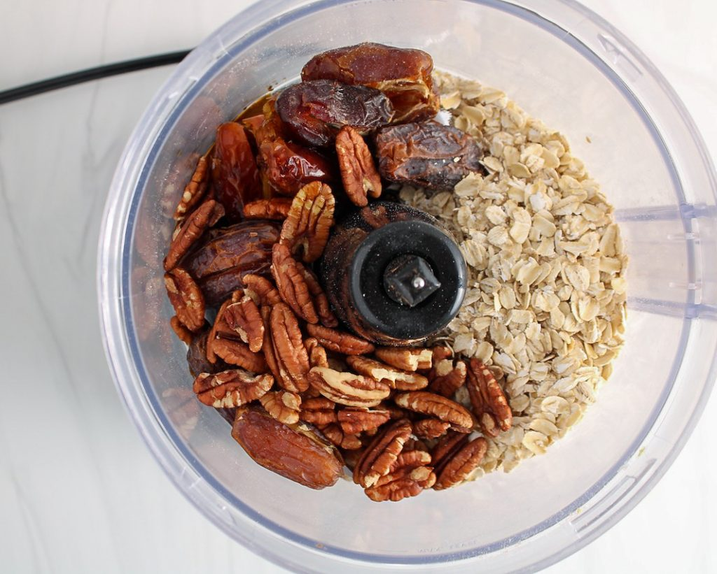 The picture shows the inside of a food processor containing raw oats, pecans and dates.