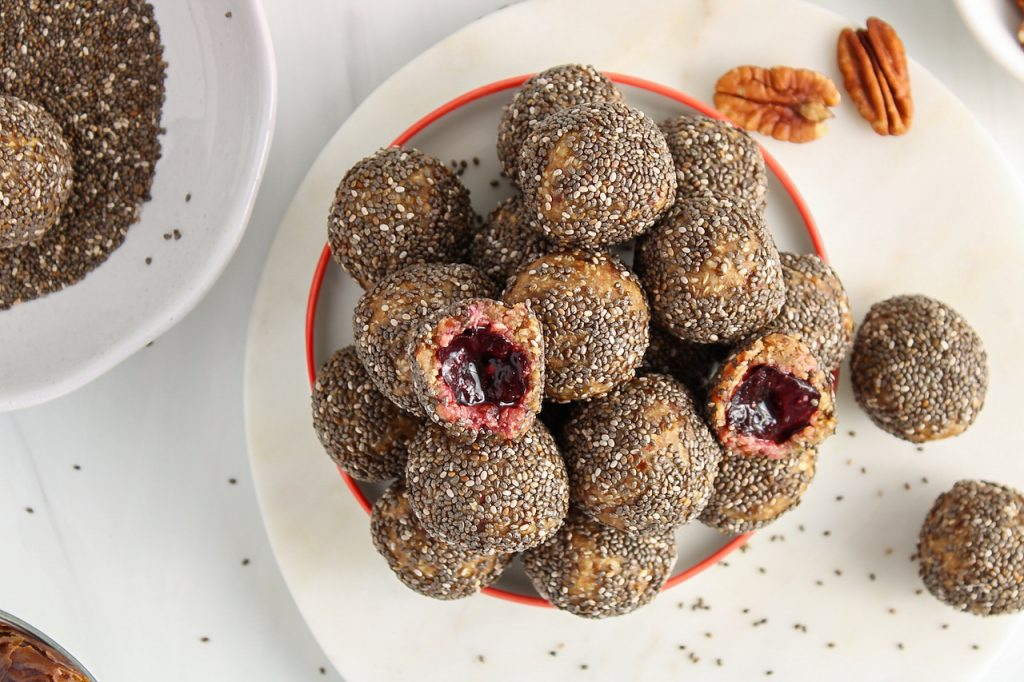 There are multiple vanilla cherry energy balls pilled up on a white plate with of them cut in half to show the cherry inside. There are more chia seeds on the side as well as a few pecans.