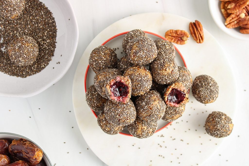 There are multiple vanilla cherry energy balls pilled up on a white plate with of them cut in half to show the cherry inside. There are more chia seeds on the side as well as a few pecans and dates.