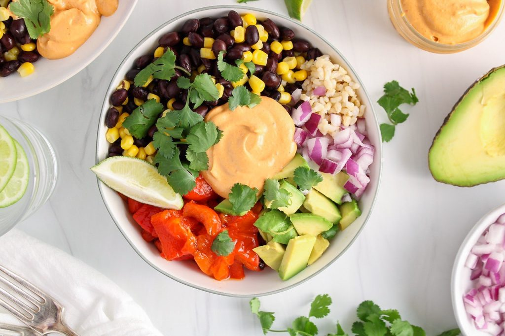 There is a white bowl containing a Mexican buddha bowl made with brown rice, red onion, black bean, corn, roasted red pepper, diced avocado, cilantro, lime wedges and a homemade vegan chipotle mayo. Surrounding the buddha bowl, there are small bowls with more chipotle mayo, red onion, avocado and cilantro as well as a white hand towel, 2 forks and a glass of water.