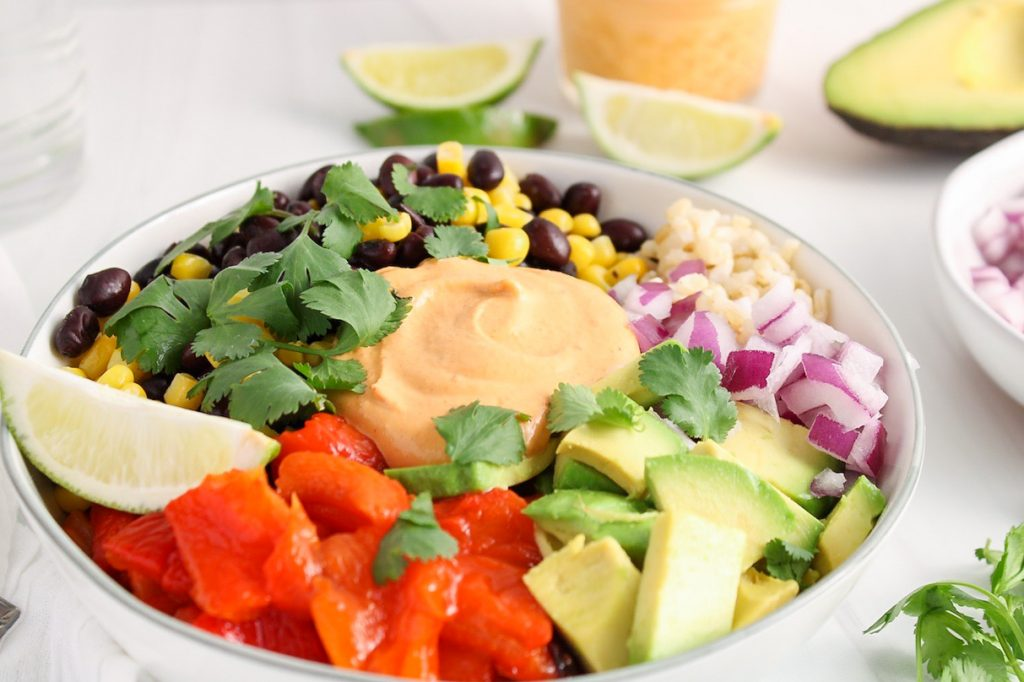 There is a white bowl containing a Mexican buddha bowl made with brown rice, red onion, black bean, corn, roasted red pepper, diced avocado, cilantro, lime wedges and a homemade vegan chipotle mayo. Surrounding the buddha bowl, there is more chipotle mayo, red onion, avocado and lime wedges.