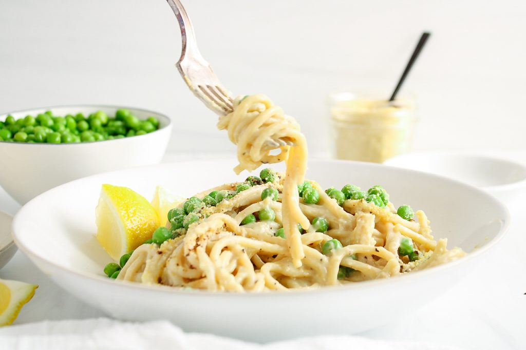 There is a fork holding a few noodles that are soaked in a creamy sauce and topped with green peas with a side of lemon wedges. There are more peas and a vegan parmesan cheese in a glass container in the background.