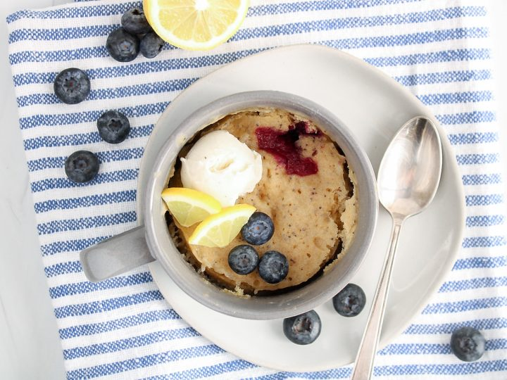 There is a lemon blueberry mug cake in a grey mug that's on a plate with a spoon on the side. There are also a few fresh blueberries on the side and the plate is on a white and blue towel.