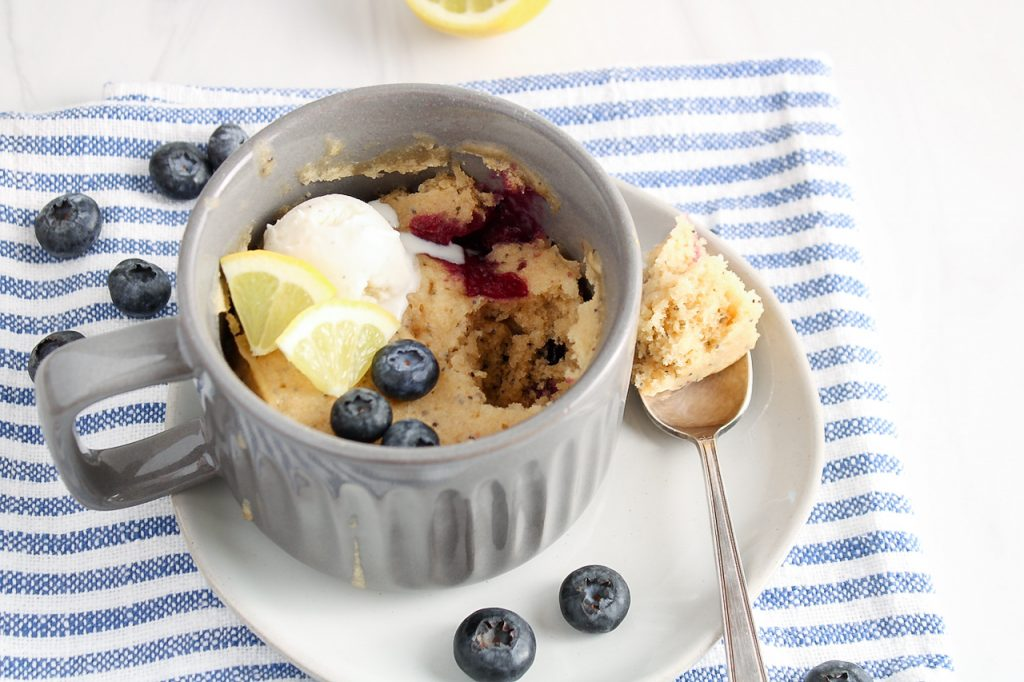 There is a lemon blueberry mug cake in a grey mug that's on a plate with a spoon on the side. There are also a few fresh blueberries on the side and the plate is on a white and blue towel. There is also a bite off the cake with some of the cake on the spoon.