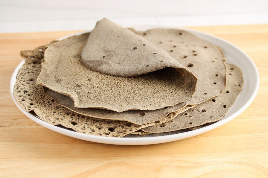There are a few buckwheat wraps piled on top of each other on a plate.
