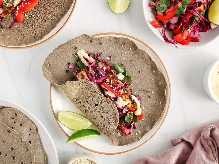 There is a buckwheat wrap topped with tofu and a red cabbage slaw with the sides of the wraps slightly wrapped on top of the filling. There are more wraps, slaw and a pink hand towel on the side.