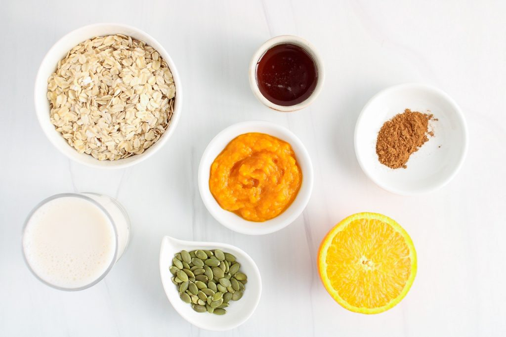 There are a few small bowls containing the ingredients to make this recipe: pumpkin purée, rolled oats, maple syrup, pumpkin spices, pumpkin seeds, vegan milk and half of an orange.