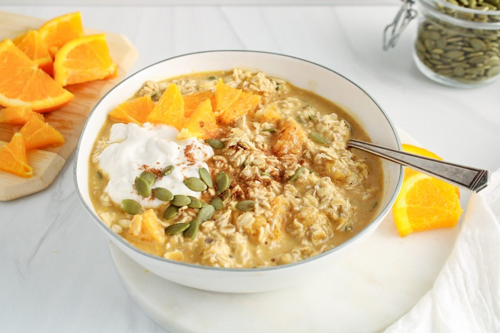 Showing is a white bowl with a orange and pumpkin overnight oats that's topped with vegan yogurt, diced orange and pumpkin seeds. There are more pumpkin seeds in a jar on the side as well as more diced orange.