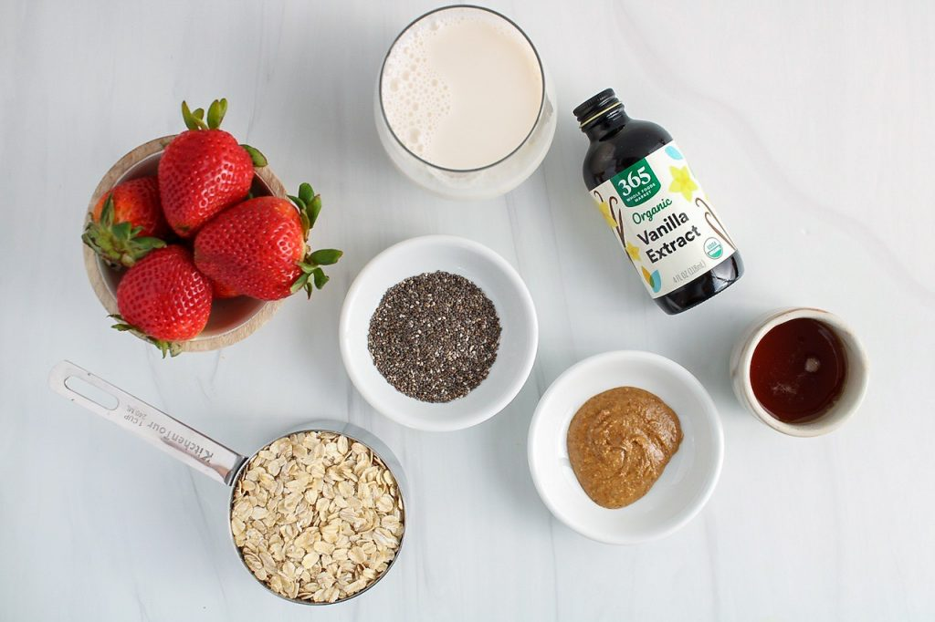 There are a few small bowls with almond butter, chia seeds, vanilla extract, vegan milk, raw oats and fresh strawberries.