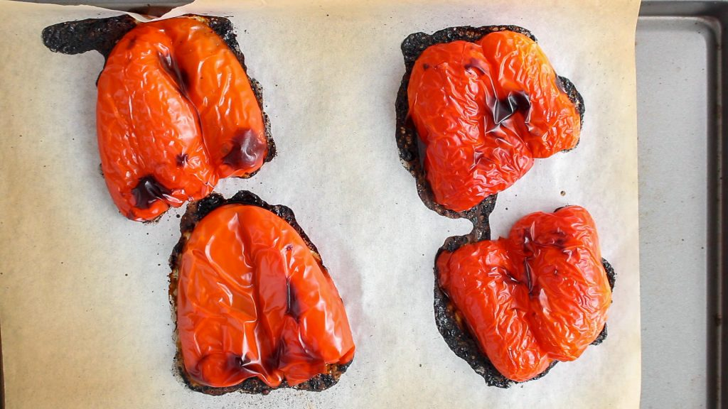 There are 4 halves of roasted red pepper on a baking sheet.