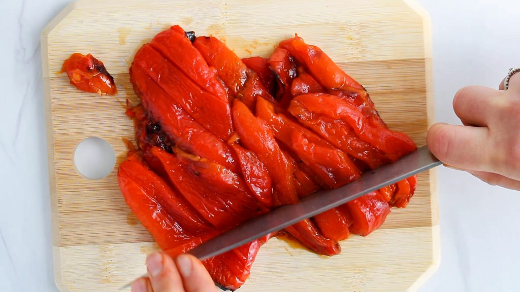 There are hand holding a knife and chopping roasted red pepper on a wooden board.
